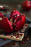Bloody red ripe pomegranate over traditional pattern Turkish til Royalty Free Stock Photography