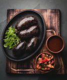 Bloody sausages - chilean preta on iron plate, top view, grey slate background Stock Photo