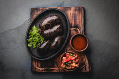 Bloody sausages - chilean preta on iron plate, top view, grey slate background Royalty Free Stock Photos
