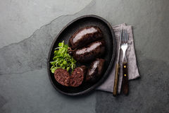Bloody sausages - chilean preta on iron plate, top view, grey slate background Stock Image