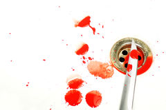 Bloody Scene. A bloody knife set on a white background with blood splatters over a plug hole in a bath Stock Photography