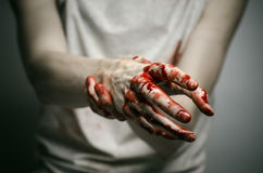 Bloody theme lone murderer: the murderer shows bloody hands and experiencing depression and pain. Studio Royalty Free Stock Images