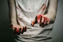 Bloody theme lone murderer: the murderer shows bloody hands and experiencing depression and pain Stock Photo