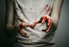 Bloody theme lone murderer: the murderer shows bloody hands and experiencing depression and pain. Studio Royalty Free Stock Photography
