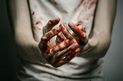 Bloody theme lone murderer: the murderer shows bloody hands and experiencing depression and pain Royalty Free Stock Photography