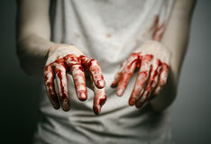 Bloody theme lone murderer: the murderer shows bloody hands and experiencing depression and pain. Studio Royalty Free Stock Image