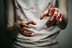 Bloody theme lone murderer: the murderer shows bloody hands and experiencing depression and pain Stock Photography