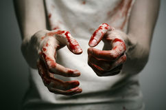 Bloody theme lone murderer: the murderer shows bloody hands and experiencing depression and pain. Studio Royalty Free Stock Photo