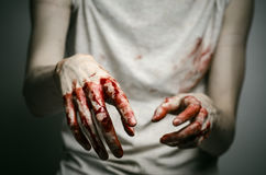 Bloody theme lone murderer: the murderer shows bloody hands and experiencing depression and pain. Studio Stock Photography