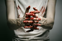 Bloody theme lone murderer: the murderer shows bloody hands and experiencing depression and pain Stock Photos