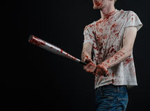 Bloody topic: The guy in a bloody T-shirt holding a bloody bat on a black background Stock Photos
