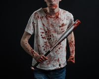 Bloody topic: The guy in a bloody T-shirt holding a bloody bat on a black background Royalty Free Stock Photography