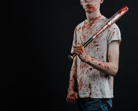 Bloody topic: The guy in a bloody T-shirt holding a bloody bat on a black background Royalty Free Stock Images
