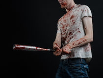Bloody topic: The guy in a bloody T-shirt holding a bloody bat on a black background Stock Photography