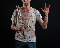Bloody topic: The guy in a bloody T-shirt holding a bloody bat on a black background Royalty Free Stock Photos