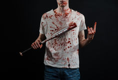 Bloody topic: The guy in a bloody T-shirt holding a bloody bat on a black background Royalty Free Stock Image