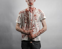 Bloody topic: The guy in a bloody T-shirt holding a bloody bat on a white background Stock Photo