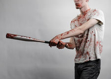 Bloody topic: The guy in a bloody T-shirt holding a bloody bat on a white background Royalty Free Stock Images