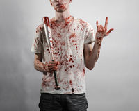Bloody topic: The guy in a bloody T-shirt holding a bloody bat on a white background Stock Photos
