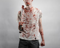 Bloody topic: The guy in a bloody T-shirt holding a bloody bat on a white background Royalty Free Stock Image