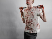 Bloody topic: The guy in a bloody T-shirt holding a bloody bat on a white background Royalty Free Stock Photos