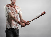 Bloody topic: The guy in a bloody T-shirt holding a bloody bat on a white background Royalty Free Stock Photography