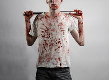 Bloody topic: The guy in a bloody T-shirt holding a bloody bat on a white background Stock Photography