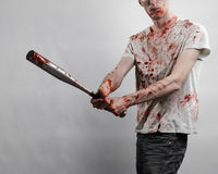 Bloody topic: The guy in a bloody T-shirt holding a bloody bat on a white background Stock Images