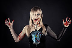 Bloody vampire with a lantern Royalty Free Stock Photos