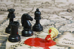Bloody War. Chess stones on a map, 3 blacks against 1 white, with blood scene Royalty Free Stock Image