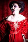 Bloody woman. Portrait of a bloodthirsty female vampire over red vintage background Stock Photo