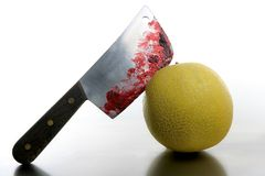 Bloody yellow melon killed by knife. Wound with blood metaphor stock photography