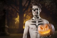 Bloody zombie man with brains out holding halloween pumpkin. Horror. Halloween. royalty free stock photo