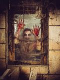 Bloody zombie at the window. Photo of a zombie outside a window that is covered with blood, spiderwebs and filth Royalty Free Stock Photos