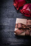 Bloomed red roses wrapped giftbox on wooden Stock Photos