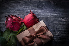 Bloomed rosebuds packed present box on wooden Stock Photo