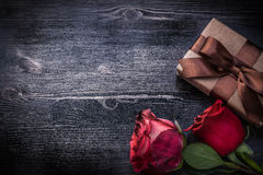 Bloomed rosebuds wrapped present box on wooden Royalty Free Stock Images