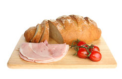 Bloomer loaf ham and tomatoes. Freshly baked bloomer loaf with ham and tomatoes on a wooden board isolated against white Royalty Free Stock Photo