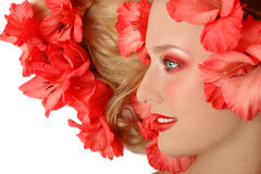 Blooming. Beautiful girl lying on white background with cornflags in her blond hair stock image