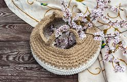 Blooming cherry sprigs in knitted pottle with handles on natural blurry background royalty free stock photo