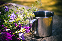 Blooming flowers and metal mug on a table Stock Images