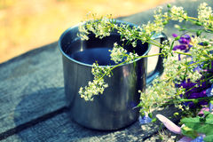 Blooming flowers and metal mug on a table Stock Photos