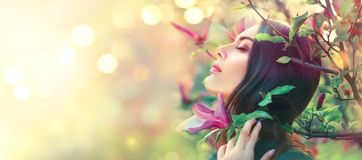 Free Blooming Magnolia Trees. Beauty Young Woman Touching And Smelling Spring Magnolia Flowers Royalty Free Stock Photos - 116550518