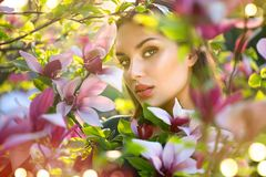 Blooming magnolia trees. Beauty young woman touching and smelling spring magnolia flowers Stock Photography