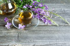 Blooming Sally, collected and dried brewing herbal tea useful scattered on the wooden background with flowers and a cup. Of tea. selective Focus Stock Photo