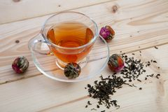 Tea balls. Blooming tea balls with cup of tea on table stock photography