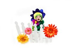 Blooming where you are planted. Baby girl, dressed in flower costume, sits behind a white picket fence where she is planted.  She is laughing and blossoming as Royalty Free Stock Photography