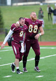Bloomsburg football players walk off field. BLOOMSBURG, PA - NOVEMBER 6: Bloomsburg tight end Ben Weaber (#88) and quarterback Pat Carey celebrate a 61-35 win in Royalty Free Stock Image