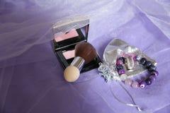 Bloos en weerspiegel, borstel, bel en armband op een purpere stoffenachtergrond Vrouwen` s schoonheidsmiddelen en toebehoren royalty-vrije stock afbeelding