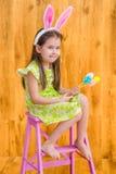Blootvoets meisje die roze witte konijn of konijntjesoren dragen en bos van kleurrijke eieren houden Stock Foto